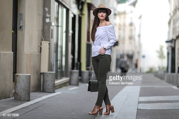 Nikita Wong is wearing Texto brown shoes Zara green jeans a Chicwish white top a Zara brown hat and a SaintLaurent bag during a street style session...