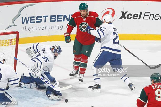 Nikita Zaitsev and goalie Jhonas Enroth of the Toronto Maple Leafs defend their goal against Chris Stewart of the Minnesota Wild during the game on...