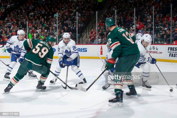 Nikita Zaitsev and William Nylander of the Toronto Maple Leafs battle for the puck with Zack Mitchell and Eric Staal of the Minnesota Wild during the...