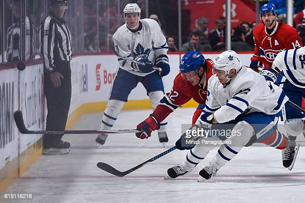 Nikita Zaitsev of the Toronto Maple Leafs and Artturi Lehkonen of the Montreal Canadiens chase the puck during the NHL game at the Bell Centre on...