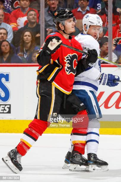 Nikita Zaitsev of the Toronto Maple Leafs and Matthew Tkachuk of the Calgary Flames battle for position in an NHL game against the Toronto Maple...