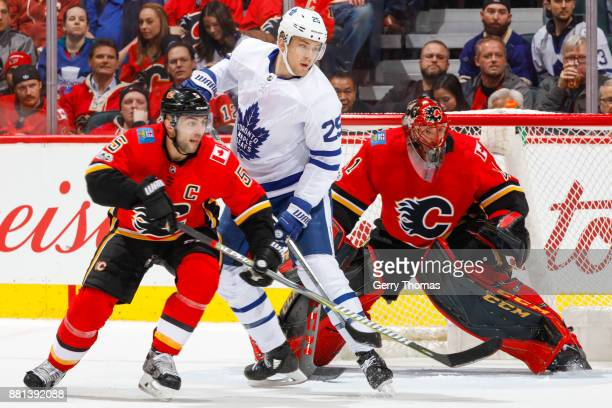 Nikita Zaitsev of the Toronto Maple Leafs looks for a pass between Mark Giordano and Goalie Mike Smith of the Calgary Flames in an NHL game against...