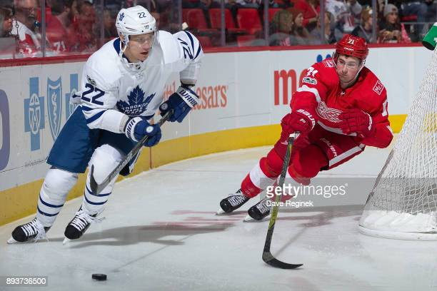 Nikita Zaitsev of the Toronto Maple Leafs skates with the puck behind the net in front of Dylan Larkin of the Detroit Red Wings during an NHL game at...