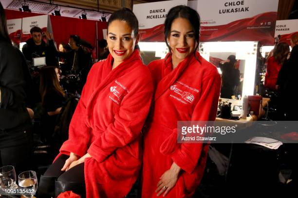 Nikki Bella and Brie Bella pose backstage during The American Heart Association's Go Red for Women Red Dress Collection 2019 at Hammerstein Ballroom...