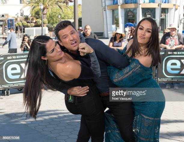Nikki Bella and Brie Bella wrestle Mark Wright at 'Extra' at Universal Studios Hollywood on October 26 2017 in Universal City California