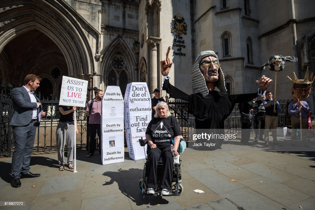 Nikki Kenward (C) from the group Distant Voices, who oppose the liberalisation of euthanasia laws, poses in front of a demonstration featuring a giant puppet of a judge outside the Royal Courts of Justice, Strand on July 17, 2017 in London, England. Noel Conway, 67, who is terminally ill with motor neurone disease, is seeking a legal challenge on the law banning assisted dying.