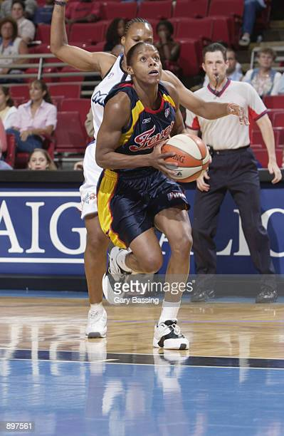 Nikki McCray of the Indiana Fever looks to the basket followed by Elaine Powell of the Orlando Miracle in the game on June 11 2002 at TD Waterhouse...