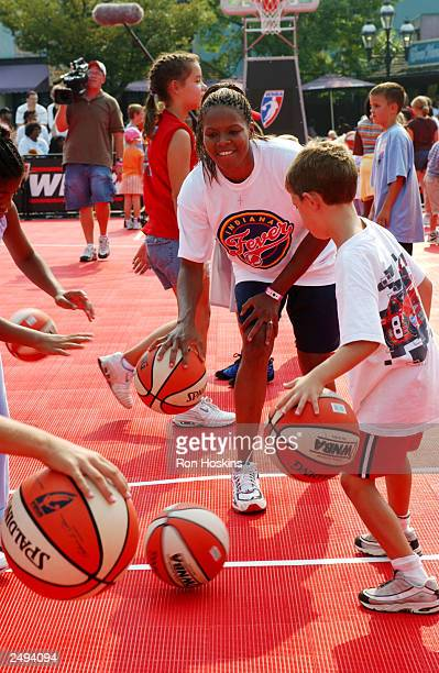 Nikki McCray of the Indiana Fever works with kids on their dribbling skills during a WNBA basketball clinic September 14 2003 at Kings Island in...