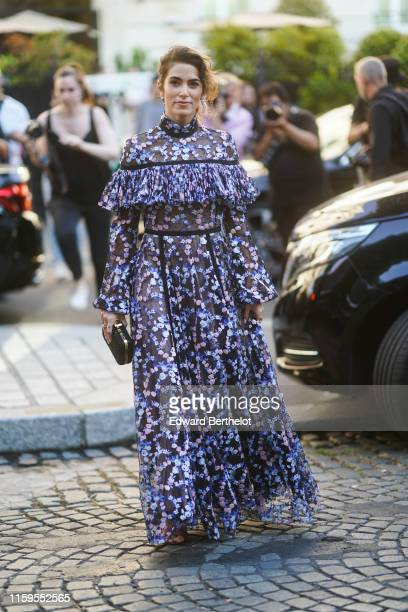 Nikki Reed wears a ruffled and fringed floral print mesh dress, a clutch, outside Giambattista Valli, during Paris Fashion Week -Haute Couture...