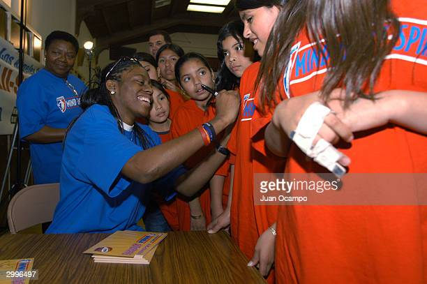 Nikki Teasley of the Los Angeles Sparks autographs tee shirts for children as part of the WNBA Mind Body and Spirit program on February11 2004 at...