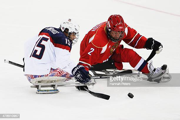 Nikko Landeros of the USA competes with Aleksei Lysov of Russia during the ice sledge hockey gold medal game between the Russian Federation and the...