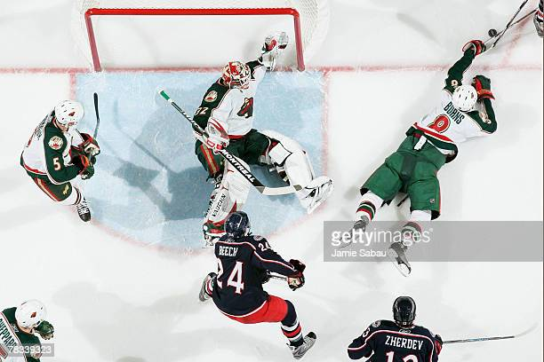 Niklas Backstrom and Brent Burns of the Minnesota Wild go down on the ice to keep Rick Nash of the Columbus Blue Jackets from scoring as Kim Johnsson...