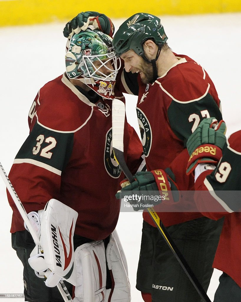 Niklas Backstrom #32 and Mike Rupp #27 of the Minnesota Wild celebrate a win of the game against the Vancouver Canucks on March 10, 2013 at Xcel Energy Center in St Paul, Minnesota. The Wild defeated the Canucks 4-2.