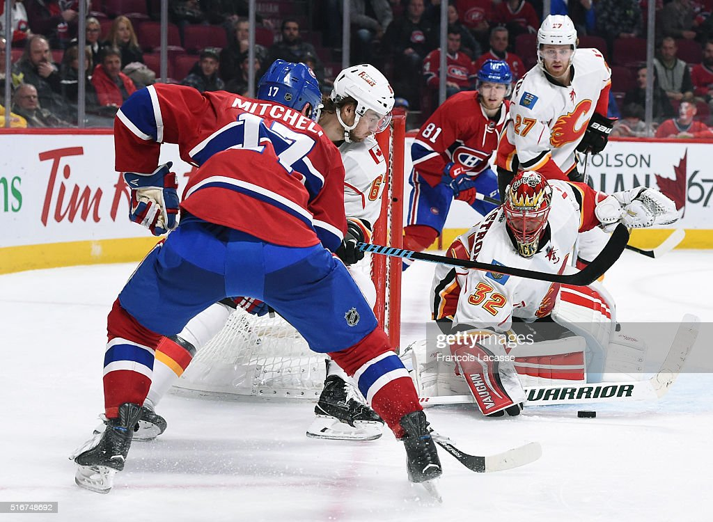 Niklas Backstrom #32 of the Calgary Flames stops a shot by Torrey Mitchell #17 of the Montreal Canadiens in the NHL game at the Bell Centre on March 20, 2016 in Montreal, Quebec, Canada.