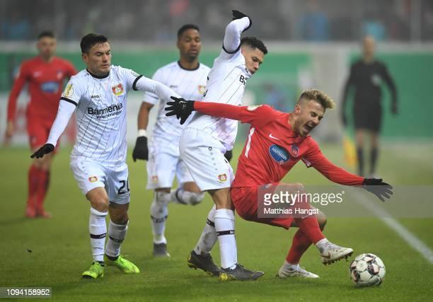 Niklas Dorsch of 1.FC Heidenheim 1846 is challenged by Charles Aranguiz of Bayer 04 Leverkusen and Paulo Henrique Sampaio Filho of Bayer 04...