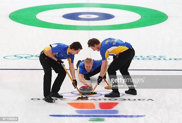 Niklas Edin of Sweden releases the stone as Fredrik Lindberg and Viktor Kjaell sweep in the Men's Bronze Medal game between Sweden and Switzerland on...