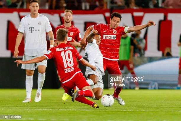 Niklas Geisler of Energie Cottbus, Thiago Alcantara of FC Bayern Muenchen and Dimitar Rangelov of Energie Cottbus battle for the ball during the DFB...