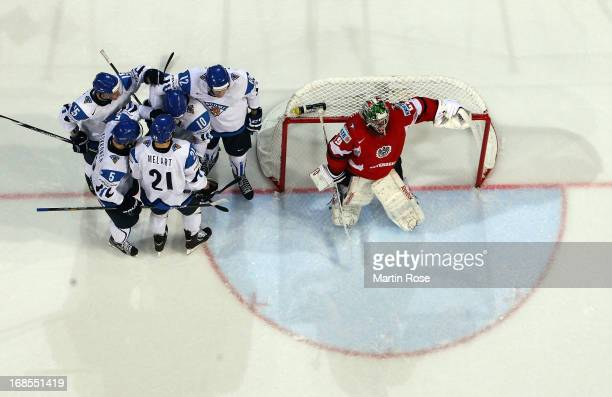 Niklas Hagman of Finland celebrate with his team mates after scoring while Bernhard Starkbaum , goaltender of Austria looks dejected during the IIHF...
