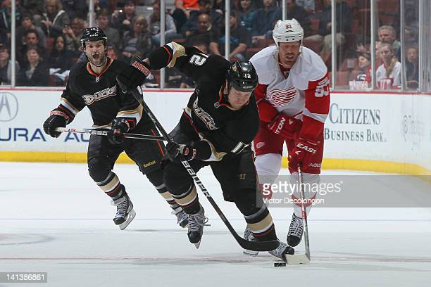 Niklas Hagman of the Anaheim Ducks controls the puck through the netural zone as he takes a slash from Johan Franzen of the Detroit Red Wings during...