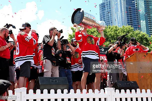 Niklas Hjalmarsson, defenseman for the Chicago Blackhawks, raises and kisses the Stanley Cup Trophy during the Chicago Blackhawks' 2013 Stanley Cup...