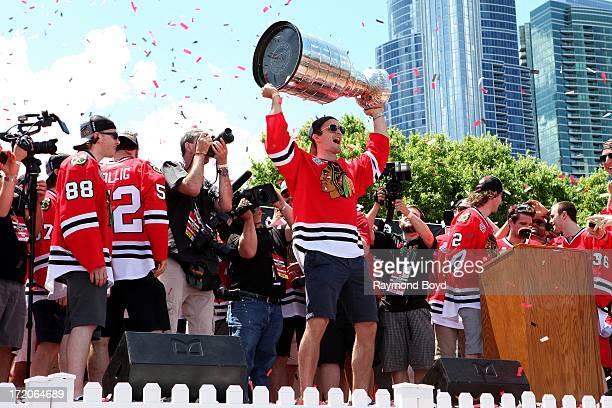 Niklas Hjalmarsson, defenseman for the Chicago Blackhawks, raises the Stanley Cup Trophy during the Chicago Blackhawks' 2013 Stanley Cup Championship...