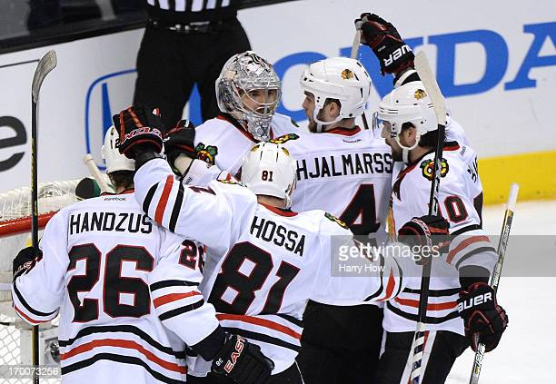 Niklas Hjalmarsson Michal Handzus Marian Hossa and Patrick Sharp of the Chicago Blackhawks gather around goaltender Corey Crawford after they...