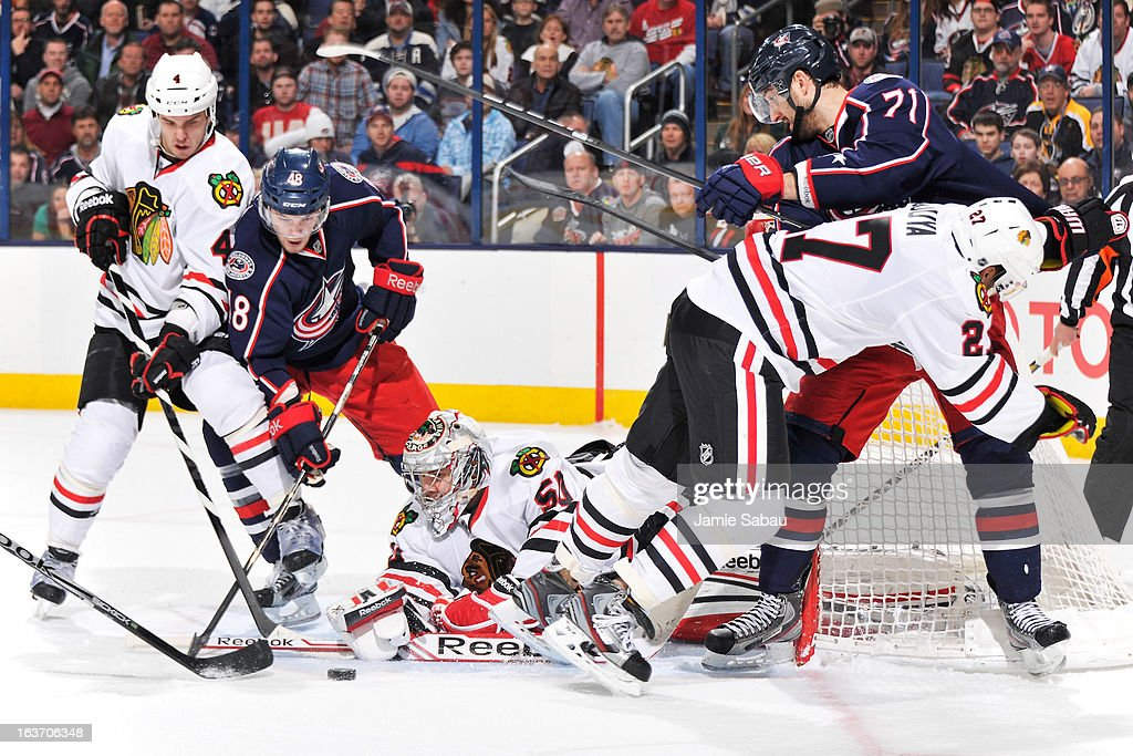 Niklas Hjalmarsson #4 of the Chicago Blackhawks and Cody Goloubef #48 of the Columbus Blue Jackets battle for a loose puck as goaltender Corey Crawford #50 of the Chicago Blackhawks makes a save during the third period on March 14, 2013 at Nationwide Arena in Columbus, Ohio. Chicago defeated Columbus 2-1 in a shootout.