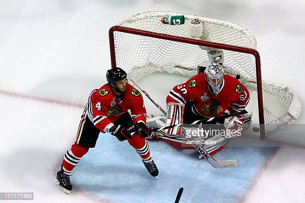 Niklas Hjalmarsson of the Chicago Blackhawks attempts to clear a rebound in front of Corey Crawford in Game Five of the 2013 NHL Stanley Cup Final at...