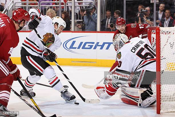 Niklas Hjalmarsson of the Chicago Blackhawks attempts to clear the puck away from goaltender Corey Crawford in Game Five of the Western Conference...