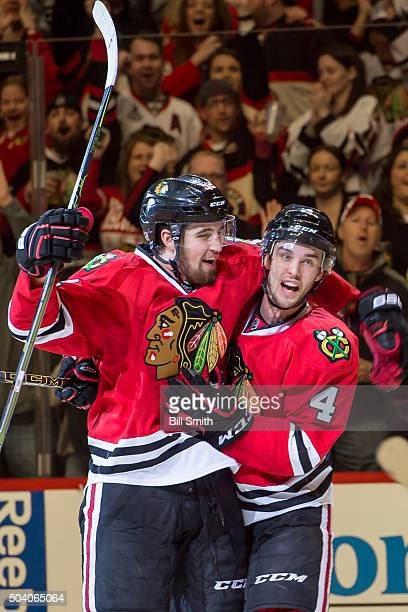 Niklas Hjalmarsson of the Chicago Blackhawks celebrates with Erik Gustafsson after scoring against the Buffalo Sabres in the first period of the NHL...