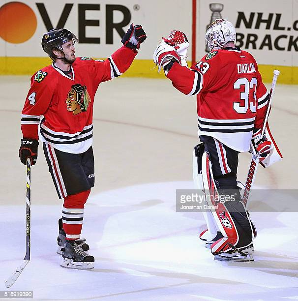 Niklas Hjalmarsson of the Chicago Blackhawks congratulates Scott Darling after a win over the Boston Bruins at the United Center on April 3 2016 in...