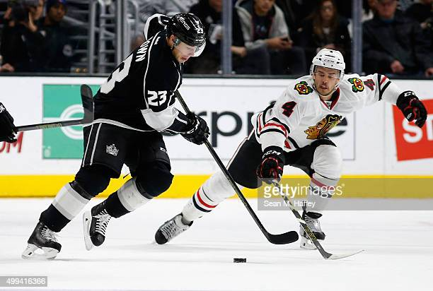 Niklas Hjalmarsson of the Chicago Blackhawks defends against Dustin Brown of the Los Angeles Kings during a game at Staples Center on November 28...