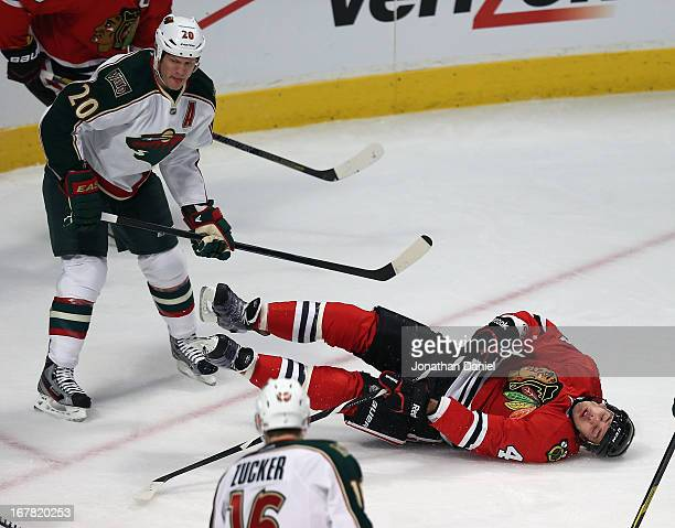 Niklas Hjalmarsson of the Chicago Blackhawks hits the ice after being shoved down by Ryan Suter of the Minnesota Wild in Game One of the Western...