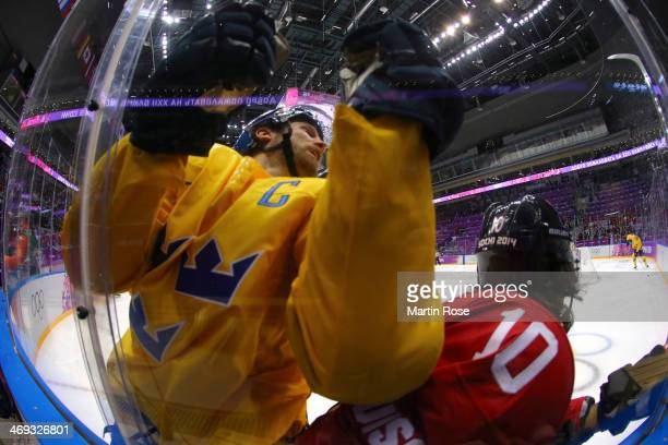 Niklas Kronwall of Sweden and Andres Ambuhl of Switzerland collide against the boards in the first period during the Men's Ice Hockey Preliminary...