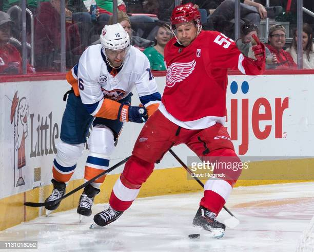 Niklas Kronwall of the Detroit Red Wings battles along the boards for the puck with Andrew Ladd of the New York Islanders during an NHL game at...