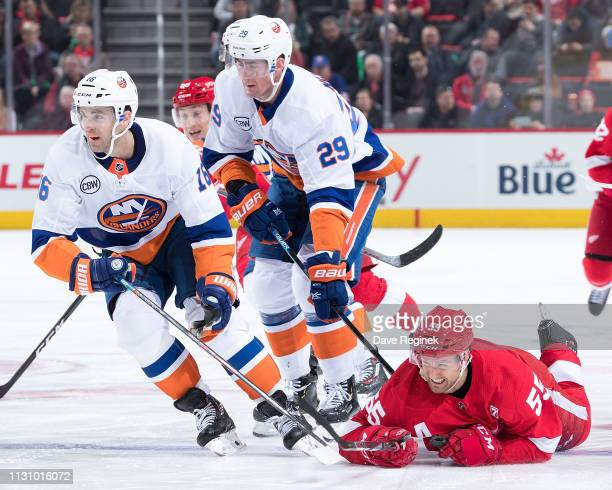 Niklas Kronwall of the Detroit Red Wings battles to the ground with Brock Nelson and Andrew Ladd of the New York Islanders during an NHL game at...
