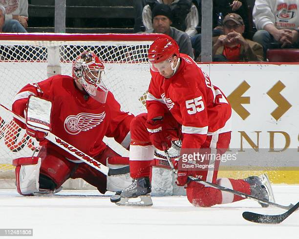 Niklas Kronwall of the Detroit Red Wings blocks a shot and breaks his stick in front of teammate goaltender Jimmy Howard during an NHL game against...