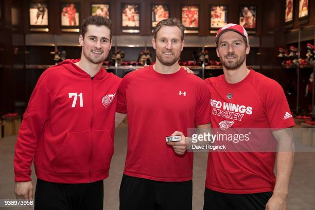 Niklas Kronwall of the Detroit Red Wings holds his 400th NHL career point puck between teammates Dylan Larkin and Darren Helm following an NHL game...