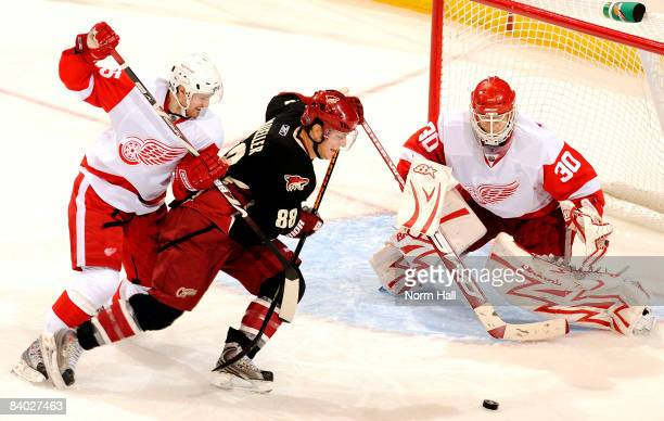 Niklas Kronwall of the Detroit Red Wings tries to prevent Peter Mueller of the Phoenix Coyotes from getting to the puck on December 13 2008 at...