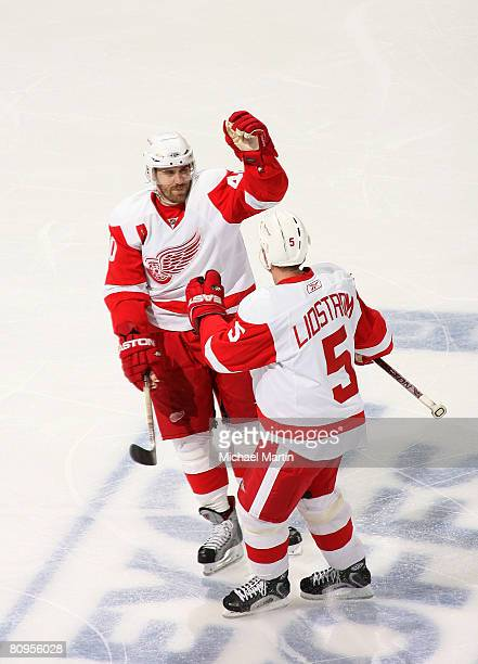 Niklas Lidstrom of the Detroit Red Wings celebrates a second period goal with teammate Henrik Zetterberg against the Colorado Avalanche during game...