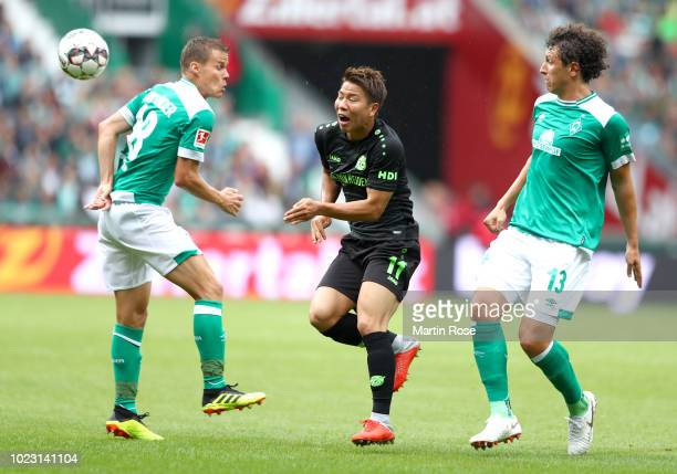 Niklas Moisander and Milos Veljkovic of Werder Bremen put pressure on Takuma Asano of Hannover 96 during the Bundesliga match between SV Werder...