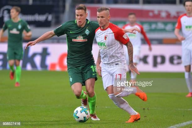 Niklas Moisander of Bremen and Jonathan Schmid of Augsburg battle for the ball during the Bundesliga match between FC Augsburg and SV Werder Bremen...