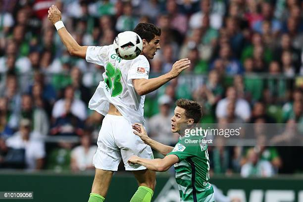Niklas Moisander of Bremen and Mario Gomez Wolfsburg compete for the ball during the Bundesliga match between Werder Bremen and VfL Wolfsburg at...