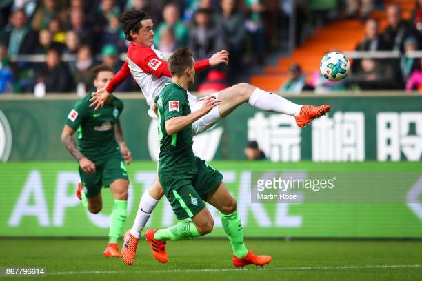 Niklas Moisander of Bremen and Michael Gregoritsch of Augsburg battle for the ball during the Bundesliga match between SV Werder Bremen and FC...