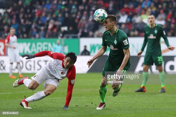Niklas Moisander of Bremen fights for the ball with Koo Jacheol of Augsburg during the Bundesliga match between FC Augsburg and SV Werder Bremen at...