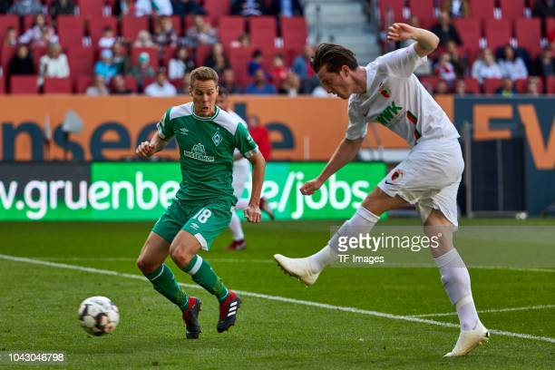 Niklas Moisander of Werder Bremen and Michael Grogoritsch of FC Augsburg battle for the ball during the Bundesliga match between FC Augsburg and SV...