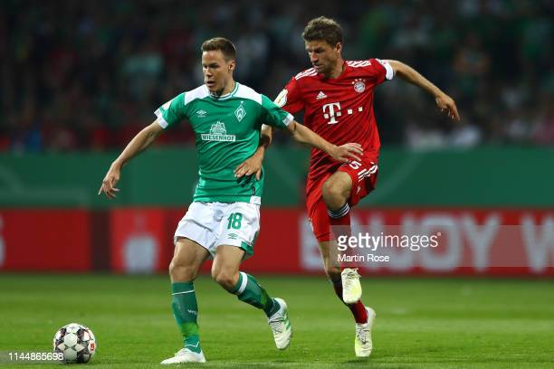 Niklas Moisander of Werder Bremen and Thomas Mueller of Bayern Munich battle for possession during the DFB Cup semi final match between Werder Bremen...