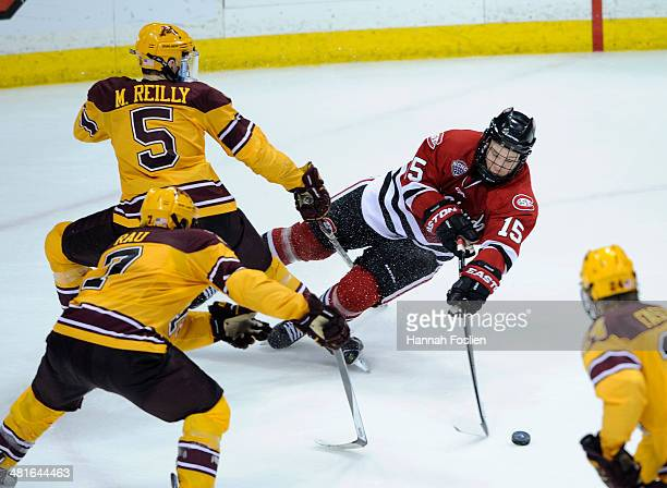 Niklas Nevalainen of the St Cloud State Huskies controls the puck as he falls to the ice against Mike Reilly Kyle Rau and Hudson Fasching of the...