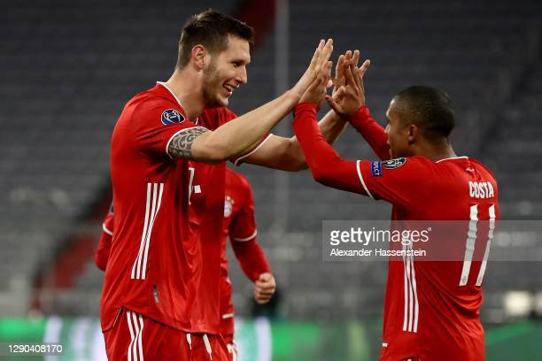 Niklas Süle of FC Bayern München celebrates scoring the opening goal with his team mate Douglas Costa during the UEFA Champions League Group A stage...