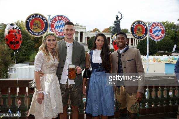 Niklas Suele and his girlfriend Melissa Halter with David Alaba and his girlfriend Shalimar Heppner attend the Oktoberfest beer festival at Kaefer...